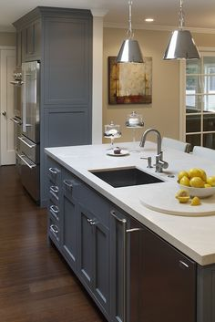 Amazing blue kitchen with floor to ceiling blue shaker kitchen cabinets paired with cream stone ...