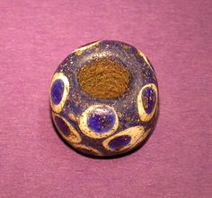 Iron Age blue glass bead from Swallowcliffe with decoration in the form of multiple eyes.