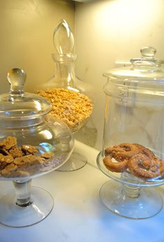 I loved this idea. Jennifer got a few glass apothecary jars (HomeGoods, Marshall's, and TJ Maxx sell these for under $15) and filled them with kitchen stuff like granola, pretzels, and cookies. Such a chic way to dress up any counter. - JAS [What about this idea for bathroom essentials???]