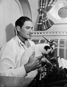 Errol Flynn and his Siamese cat Bes Mudi, in Flynn's yacht, the Zaca (1940′s)
