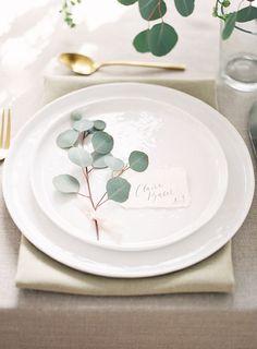 Elegant minimalism, wedding place setting, eucalyptus leaves, white plates, gold flatware // Brit.co