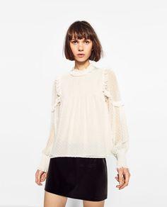 ZARA - WOMAN - БЛУЗА ОТ ПЛУМЕТИ. Блуза с дължина до ханша. Обло деколте. С дълъг ръкав. Акцент маншети и яка с ластик. Волани на рамото. Отворен гръб с копче за закопчаване. С хастар. ВИСОЧИНА НА МОДЕЛА 178 cм.