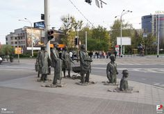 Part (2). The public art installation called Przejście, translated as Passage or Transition was installed at the cross streets in December 2005 to mark the 24th anniversary of when martial law was introduced in Poland (December 13, 1981). It was a time when many ordinary civilians were killed and went missing, which is reflected by the descending pedestrians who disappear into the Earth.