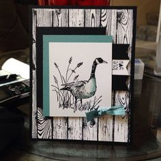 """By Julie Phillips. Stamp """"Hardwood"""" (Stampin' Up) on 5"""" x 3 3/4"""" white cardstock panel and attach to black card base. Stamp goose and grasses from """"Wetlands"""" (Stampin' Up) on 3"""" x 2 1/2"""" white cardstock panel. Layer stamped panel onto 3 1/4"""" x 2 3/4"""" solid color panel then onto same size black panel as shown. Add sentiment and bow. [Measurements are my estimates.]"""