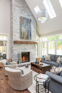 This radiant family living room features a high vaulted ceiling, custom stone fireplace and a number of large windows overlooking the private yard. Simple, refined and rustic furniture compliment the room and create a warm and inviting space. Grey Stone Fireplace, Home Fireplace, Fireplace Remodel, Living Room With Fireplace, Fireplace Design, Fireplace Mantels, Fireplace Ideas, Fireplace Windows, Stone Fireplace Makeover
