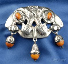 Rare Silver and Amber Brooch, Georg Jensen, c. 1909-1914, the arched floral form set with amber cabochons suspending three amber bellflowers, 3 1/2 x 3 1/2 in., no. 58, signed Georg Jensen, GI and GJ.