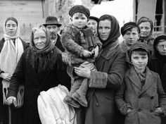 Refugees stand in a group in a street in La Gleize, Belgium on January 2, 1945, waiting to be transported from the war-torn town after its recapture by American Forces during the German thrust in the Belgium-Luxembourg salient. (AP Photo/Peter J. Carroll)