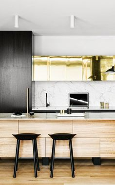 Black and white kitchen with marble backsplash, metallic cabinets and bar stools