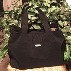 Baggallini Great Baggallini travel bag.  Black cloth with brushed Nickel hardware.  Large front and rear pocket with magnetized snap closure.  Center of bag has a zip top closure. Mesh phone pocket has been removed.  Otherwise, very good, used condition Bags Travel Bags