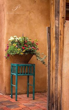 Old teal table with flowers by adobe wall looks so special