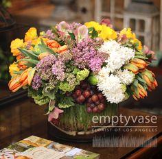Orange tulips, hyacinth,  yellow daffodils, viburnum, lilac, roses and ranunculas.