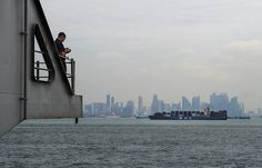 STRAIT OF MALACCA (May 25, 2013) A Sailor aboard the aircraft carrier USS Nimitz (CVN 68) photographs the city of Kuala Lumpur, Malaysia as Nimitz transits through the Strait of Malacca. Nimitz Strike Group is deployed to the U.S. 7th Fleet area of responsibility conducting maritime security operations and supporting theater security cooperation efforts. (U.S. Navy photo by Mass Communication Specialist 3rd Class Devin Wray/Released)
