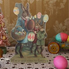 Rabbits and colored eggs have been symbols of Easter for many years. In this vintage style tabletop display, marching rabbits, dressed in their fine Easter attire, carry beautifully colored,  glittered covered eggs and seem to be determined to spread their cheer and 'good wishes' for Easter! This charming decor is perfect by itself or can be paired with any of our foil wrapped bunnies, spring chicks or can even be placed next to one of our pink  'bottle brush' Easter trees.