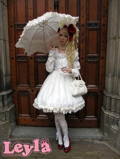 White, long-sleeved Gothic Lolita dress with matching parasol.
