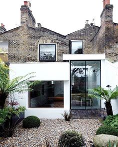 The rear of the house features Victorian brick, a modern extension, and Velfac windows. Landscape designer Matthew Wright was inspired by the art of Henri Rousseau when choosing plants to set amid the garden's Dorset pebbles. #exterior #architecture #garden #outdoor #modern #dwell Photo by @julianbroad Architecture by @williamtozerassociates Location: London, England