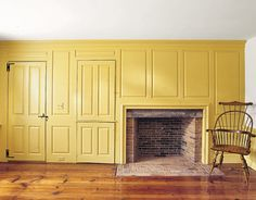 The fireplace wall of raised paneling was original to this Colonial-era home. The homeowners researched historic colors before choosing this ochre yellow.