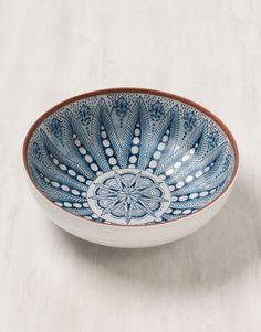 Stort målat fat i terracotta med blått mönster.