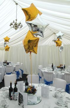 Simple yet elegant marquee decor, featuring gold and silver foil star shaped balloons as table centrepieces