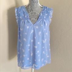 Ruffle Trim Top This beautiful pale blue top features breezy palm tree prints, pleated details, and adorable ruffle trims. Great alone or under a comfy cardigan or blazer. 100% polyester, machine washable. Elle Tops Tank Tops