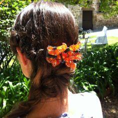Invitada con un tocado de mariposas naranjas de Naranjas Con Tocados