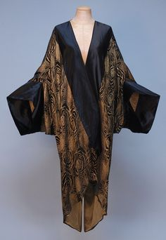 PARIS LABEL SILK and LAME COCOON STYLE EVENING COAT, c. 1920. Black satin with gold stylized rose pattern, wide satin bands at front and sleeve hem, single satin tie, lined in pale gold chiffon.