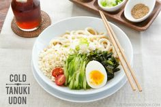 Cool off with this refreshing and delicious cold tanuki udon drizzled in umami mentsuyu and topped with cucumber, tomatoes, tenkasu, wakame, and egg.