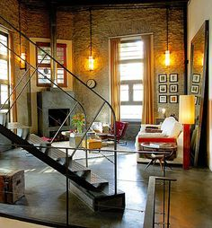 Buenos Aires home. Adore the open floorplan - and how the textured, painted walls, orangey sconces and window treatments, and plush decor warm up what could be a very industrial space.