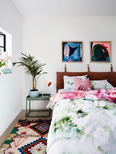 Colorful bedroom with a beautiful bedding in pink and green. Great artworks and some interior plants make this room look perfect.