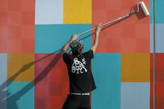 Amir applying a layer of transparent coating to the first painted wall of the former bijlmerbajes prison-turned-refugee center. Giving the grey building complex a fresh identity as the temporary home for Amsterdam's new citizens, who can participate in the project themselves..  📷 by Betul Elliatogliu    #favelapainting #amsterdampainting #bijlmerbajes #newcitizens #socialproject #art #muralart #haasandhahn