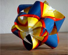 Four folded circles in a tetrahedron arrangement painted to show the closest packing of spheres.