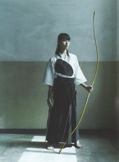 Japanese archer wearing traditional Hakama, with her yumi and archer's glove (kyudo)