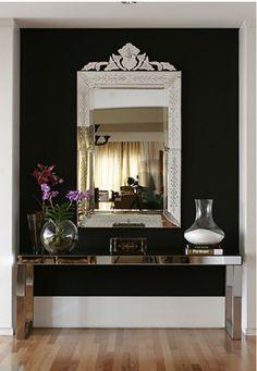 Venitian mirror & mirrored consul table againist a black backdrop.