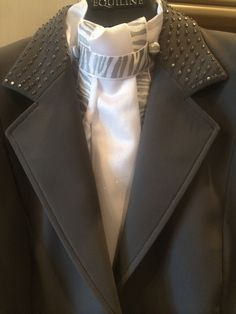 Taupe short coat with mother of pearl button trim.  Matching white satinique stock tie with iridescent zebra ribbon trim in gold and silver.