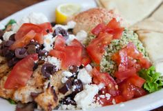 Greek Chicken is served on a bed of sauteed spinach and topped with fresh tomatoes, Greek olives, and feta cheese.  We serve it with home-made hummus and tabbouleh and locally-made, toasted pita bread.