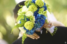 Royal blue hydrangeas, green viburnum, white roses, and maiden hair fern