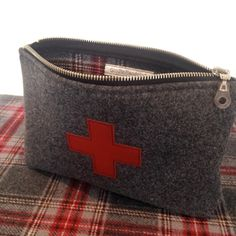 This is a 100% pure wool fabric that is thick and soft like a blanket. It is a dark grey on the outside with a red cross cut from genuine leather