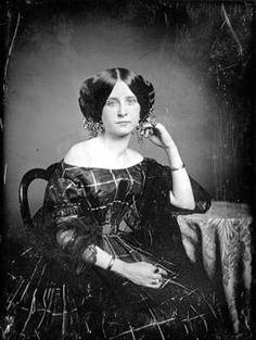 Absolutely gorgeous!  She must be wearing a jeweled hairnet. The off-the-shoulder dress suits her perfectly as does the sheer lace stole. There is a ring on her forefinger. 1840s