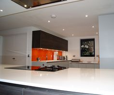 Eyes are drawn to this fluorescent orange glass splash back that creates a focal in this Watermark Kitchen.