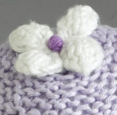 Simple free pattern for a knitted flower to add to hairbands, hats, bags and such.