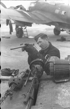 Mechanic in the maintenance of aircraft weapons, in the background a Heinkel He 111.