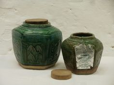 Large and small sized green glazed gingerjars with wooden lid.