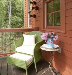 A covered stoop provides a quiet spot for reading or greeting neighbors. A grass green outdoor chair hints of the vibrant colors inside. Birdhouses, birdbaths, and plenty of flowering plants embrace the Callaway Gardens aesthetic.