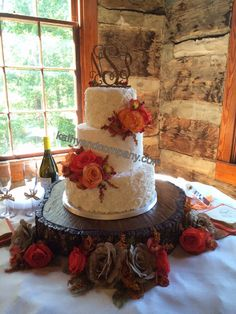 Autumn buttercream wedding cake with orange toned fresh flowers.