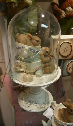 Vintage style pedestal holds two bunnies and stack of teacups.  Includes glass dome cover. Shop Shelley B Home and Holiday for more unique home decorations.
