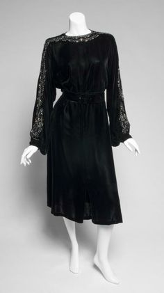 Greta Garbo Black velvet evening dress from the late 1930s. Long-sleeve tea-length dress with rhinestones, glass beads, and jais embroidery at neckline and down sleeves. Sleeves button at cinched wrist, hook and eye closure