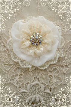 This listing is for one cream lace Gillyflower - handmade by Gilly and Jennelise. This flower is made with ivory silk, creamy net lace, white