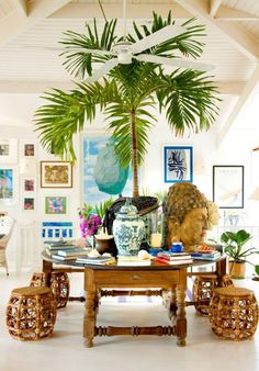 island boho....A well-accessorized center table commands attention in this tropical home where stacks of books, large-scale decorative accents, and a full palm tree create a compelling composition. The...