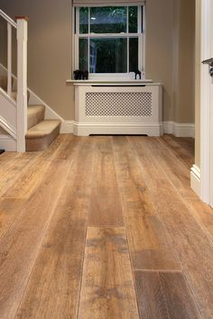 Winchester Antique engineered oak wood flooring with an aged and distressed surface to replicate a reclaimed oak board. Fitted throughout ground floor in Sunningdale Berkshire. Shown here in hallway.
