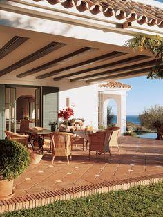 00157649. Comedor de verano bajo el porche con vigas de madera y sillones de mimbre_00157649