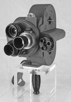Bell & Howell 35mm Eyemo 71-MM compact turret camera on clear stand. (Late-WWII model)